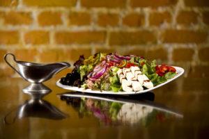 Ein Salatteller mit Dressing im Restaurant Sandmann.